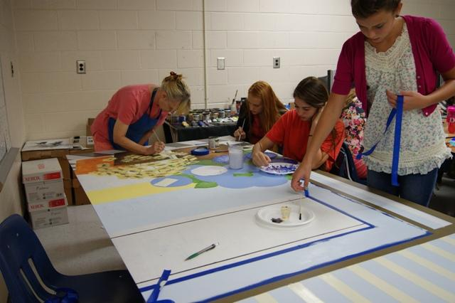 Marsha Patterson and students (from left to right) Diana Hybru, Alex Sievenpiper, and Phoebe Kinser work together to put this mural masterpiece to finish.
