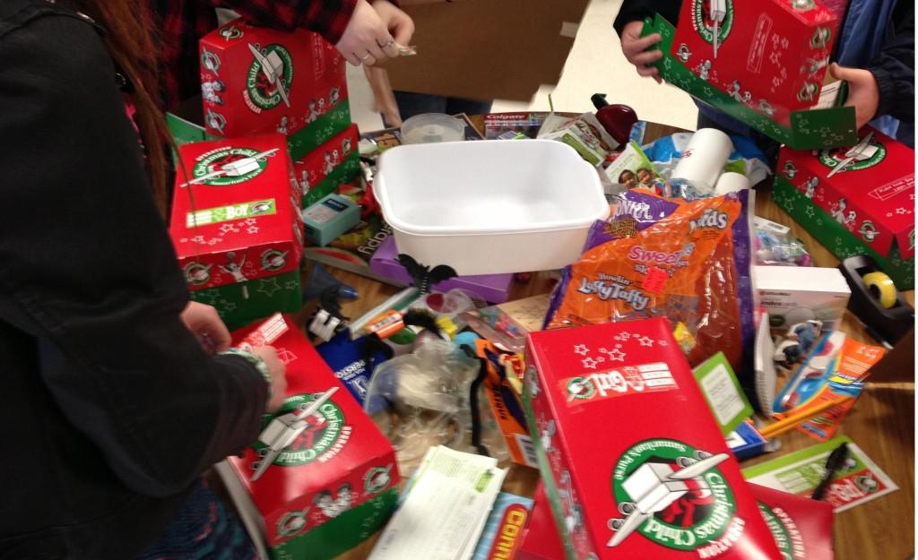Table overflowing with donations, FCCLA members work to fill up each shoe box with a variety of items.