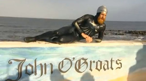 Sean Conway lays on a John O'Groats sign for a camera.