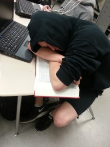 Overwhelmed with the many struggles of living in a first world country, a bedraggled student is attempting to catch up on sleep during class.