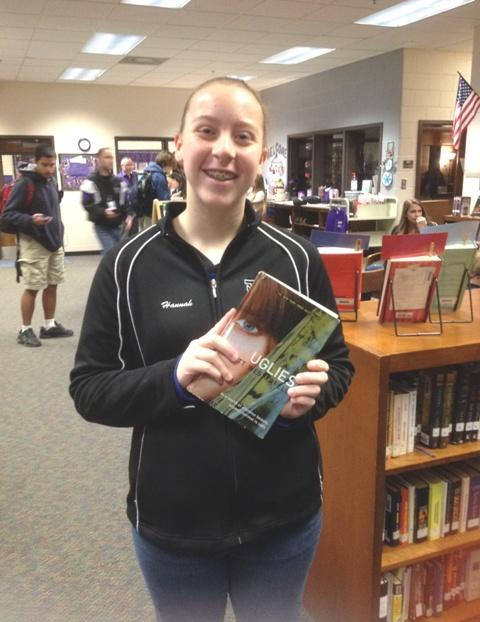Hannah Sweet holding a copy of Uglies by Scott Westerfield.