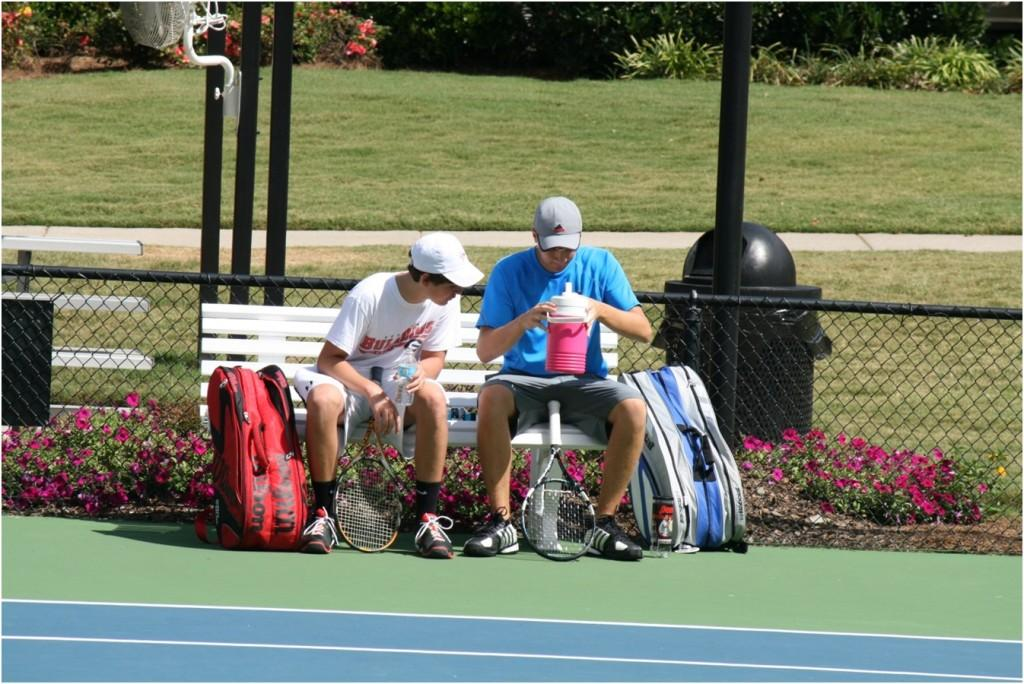 In+the+heat+of+an+outdoor+tennis+match+in+Windermere+Subdivision%2C+two+young+men+talk+strategy+and+regroup+for+their+second+set+of+doubles.+%09