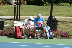In the heat of an outdoor tennis match in Windermere Subdivision, two young men talk strategy and regroup for their second set of doubles.