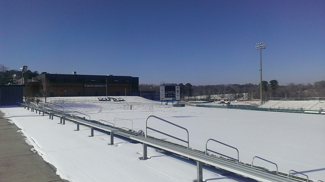 The football field is covered in the smooth, white snow.