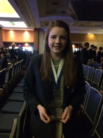Nicole Sullivan stands, proudly accepting her award for placing 2nd in the Buying & Merchandising – Online Testing category.