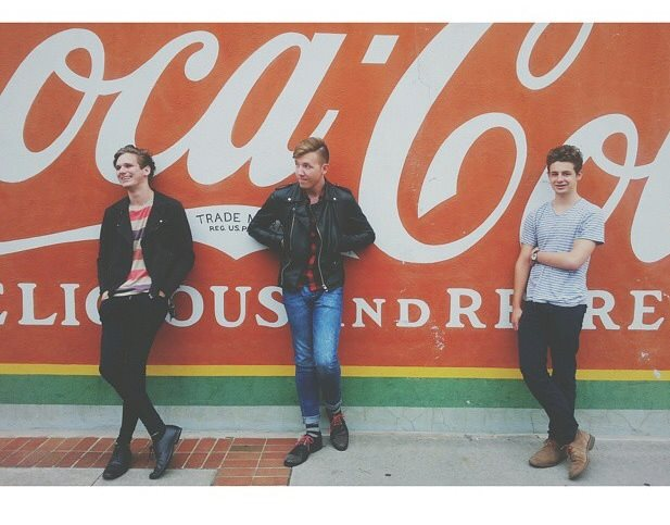 The indie rock group poses against an indie-esque Coca Cola backdrop.