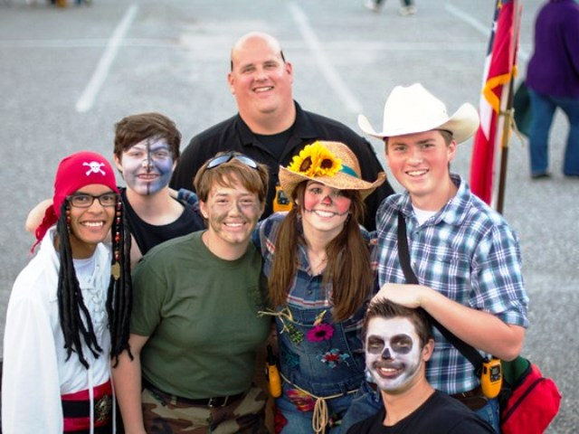 This photo is from the donation website on Officer Hodgkins behalf. He is standing with a group of students in costumes. Officer Hodgkins was hit by a truck while directing traffic on Monday, October 27 in front of Coal Mountain Elementary School.