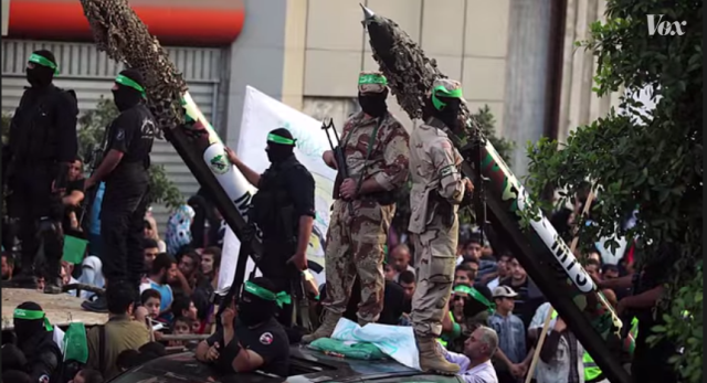Masked Hamas militants parade their weapons through the streets of Gaza.