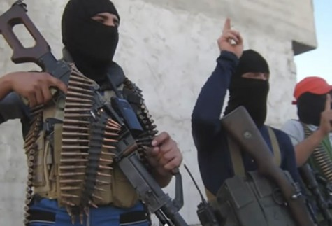 ISIS members show off their fire power, wearing masks and brandishing machineguns for a camera.