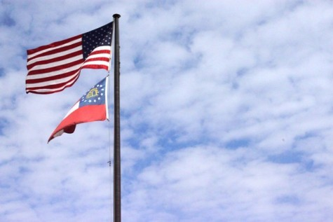 The flag of the United States flies above the flag of the US State of Georgia on a flagpole. According to US law regarding the handling of flags, the US flag must fly above a sub-national flag on a flagpole. The US flag and the flag of any other sovereign country must be placed beside each other on flagpoles of equal size.