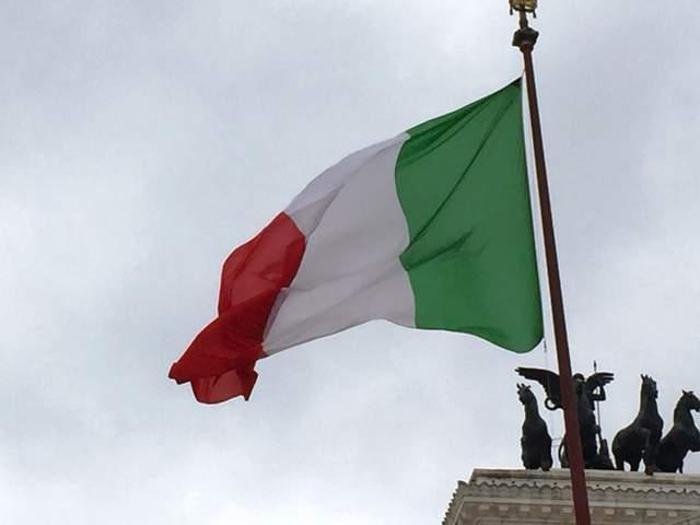 The+Italian+flag+flies+next+to+the+Altare+Della+Patria%2C+a+national+monument+dedicated+to+King+Victor+Emmanuel+II%2C+the+first+king+of+a+united+Italy.+The+gigantic+building+is+adorned+with+Corinthian+columns%2C+fountains%2C+two+rooftop+statues+of+the+Goddess+Victoria+riding+on+quadrigas+%28chariots+led+by+four+horses+abreast%29%2C+and+a+statue+of+the+king+himself.+Police+stood+inside+the+monument+to+ensure+that+crowds+did+not+linger+by+it+for+too+long.
