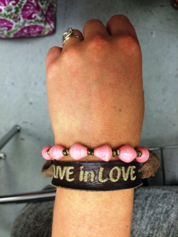 "Simple bracelets can be paired with one another to display the special meanings behind them. In this case, Senior Perri Rabbitt wears her pink, handmade bracelet from Kenya and a ""Live in Love"" bracelet to reflect her support and inspiration."
