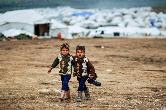 Two+Syrian+boys%2C+who+fled+from+home+with+their+family%2C+walk+back+to+their+tent+in+a+refugee+camp