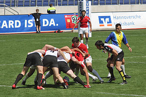 "This is a picture of a group involved in a ""scrum"" in rugby sevens. The picture comes from this article about the sport."