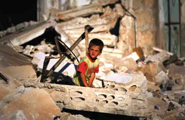 A Syrian kid savages what is left from a battlefield. He hopes to find something useful to aid him in.