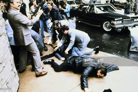 Ronald Reagan shown on the ground seconds after Hinckley fired shots. Extreme panic broke out as civilians tried to find the source of the sounds.