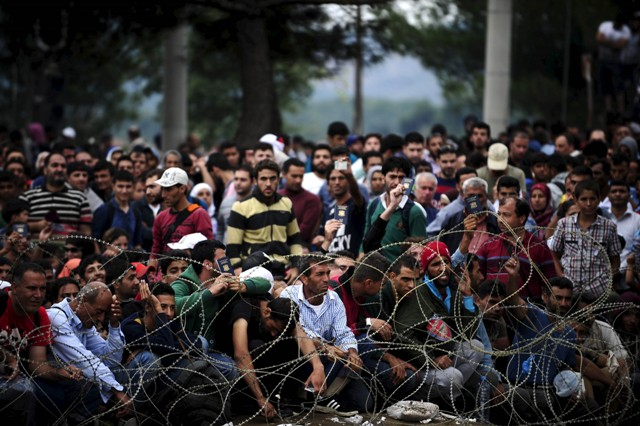Syrian Refugees being held behind barbed wire for safety.