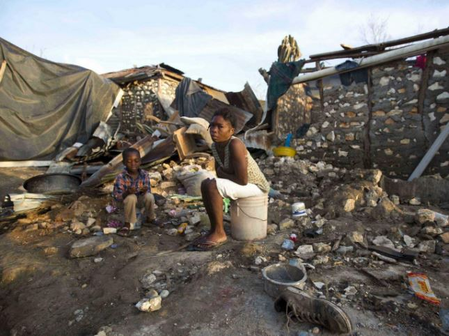 Amid a destroyed home covered in ruin, a woman and a small child sit on buckets in Jeremie, Haiti. This is only a meager fraction of all the damage done by Hurricane Matthew. (Photo obtained from independent.co.uk)