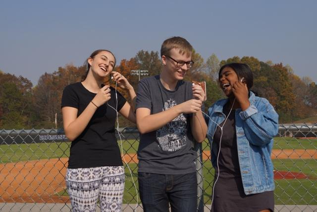 Junior Noah Smith and freshmen Melina Vergilis and Anna Anglin check out some fall tracks together by the football field. When fall comes around, calmer song choices come with it. Here are some songs to listen to with a big cup of coffee and a ton of Netflix to watch.