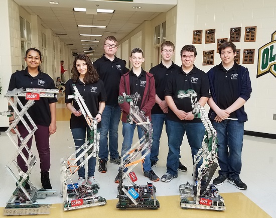Students (right to left)  Ramya Raja, Maria DeSouza, Andrew Collett, Owen Taylor, Jacob Nickles, Logan Swafford and Eric Laurin all proudly stand with their robots after competing in the VEX state championship.