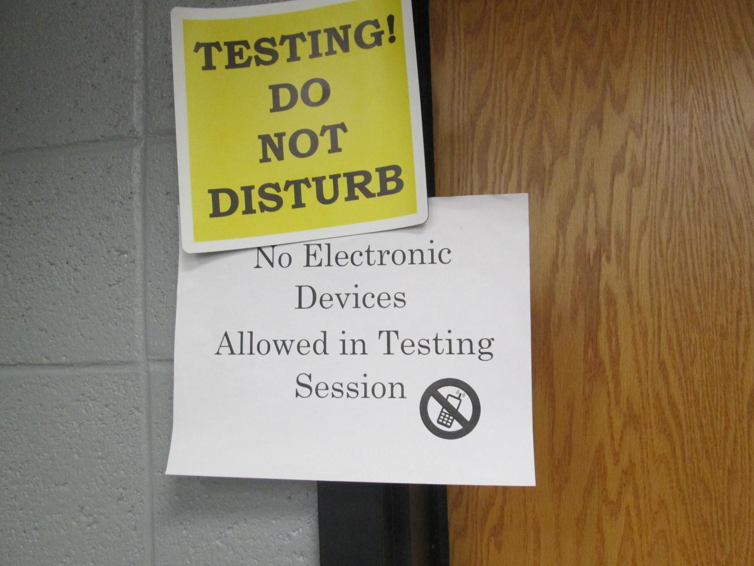 The purpose of the photo is to depict the testing room and the signs that are scattered around the schools as the event is going on. The color resembles caution, and the bold print signifies that there will be consequences if the rules are not followed adequately.
