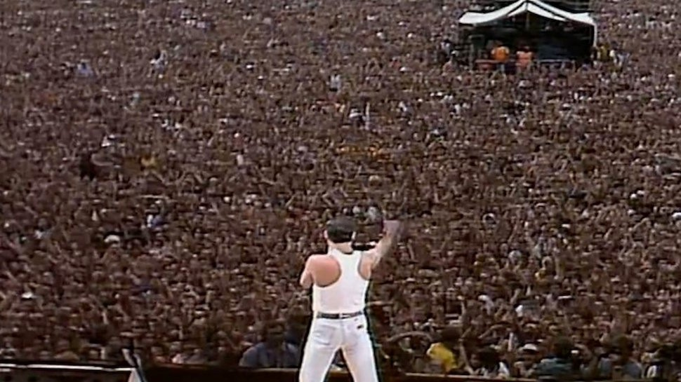 Freddie Mercury stands tall before the Live AIDS concert crowd and delivers a heartfelt performance of Queen's greatest hits. It was one of the largest concert crowds recorded. Freddy Mercury is one example of an artist who remained un-corrupt by the industry   (Photo Credits: https://www.943thedrive.ca/2018/11/16/20734/.)