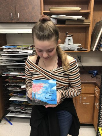 "NAHS secretary Alexa Edwards proudly holds her finished Imagination Square. Painted on the square is Bob Ross' most famous quote: ""No mistakes, only happy accidents."""