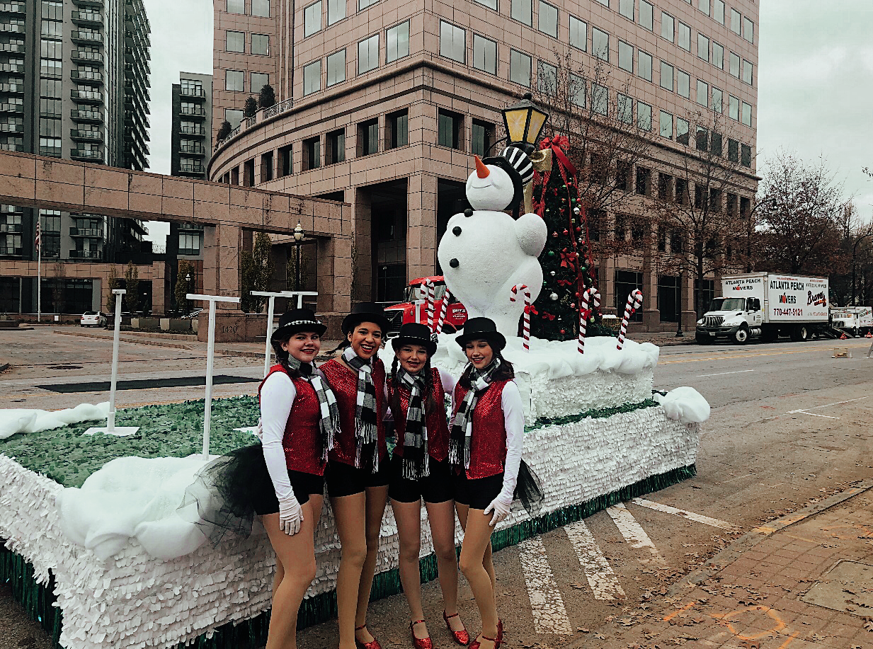Freshman Anneliese Amukamara, pictured second to the left, and her dance friends truly enjoyed dancing in the parade. The four posed in front of their frosty the snowman themed float! Photo submitted by Anneliese Amukamara.