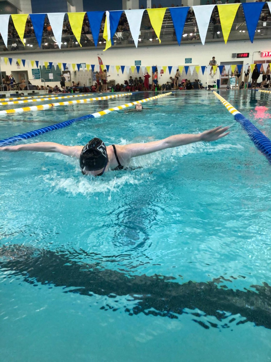 Varsity swimmer Julia Wickman practices her fly in the warm up pool with other freshman Lauren Fields. They each take turns swimming a lap before they swim their next event, the 500 freestyle.