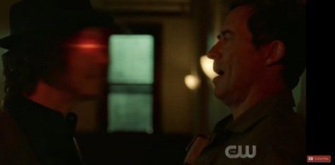Nash is talking to his hallucination. The guy in the hat is the hallucination and the guy on the wall is Nash. (Photo from the CW.)