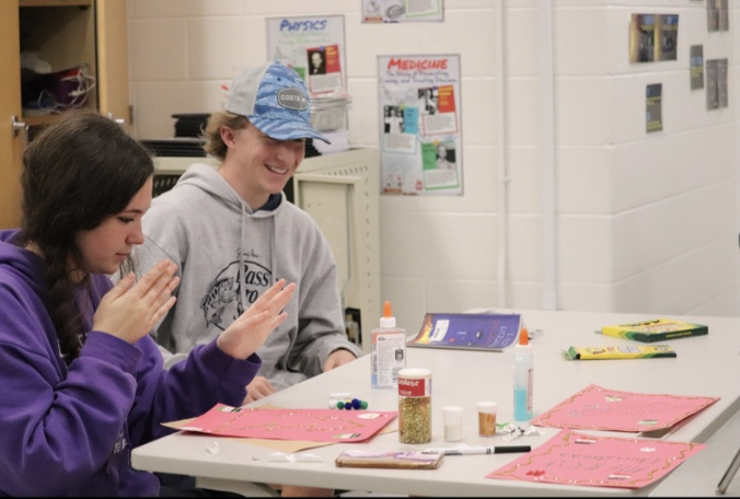 Juniors, Aspen Townley and Brodie Mizer embrace the Christmas spirit decorating cards for the National Honor Society. Photo by Ella Hill.